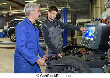 mechanics referring to a laptop for service order