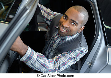 Portrait of mechanic leaning out of car