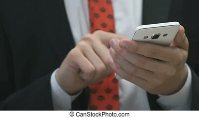Man holding the white mobile phone indoors. Close up