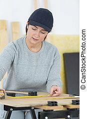 woman measuring a plywood