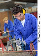 apprentice using circular saw in metallurgy workshop