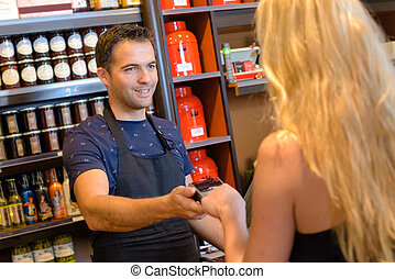woman paying for purchaces at a delicatessen