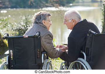 Elderly couple in wheelchairs, reaching for eachother