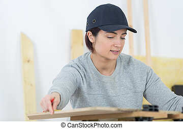 portrait of happy female woodworker drafting new project at...