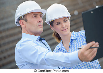 Man and woman looking at clipboard in outstretched arm