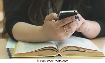 Schoolgirl views the photos using the smartphone - The...