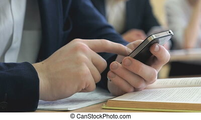 Student writes the text using a smartphone - The student...