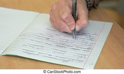 The pupil writes in a notebook in the classroom - The pupil...