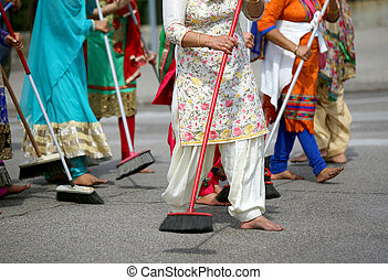 many barefoot women sweep the road during the ceremony along...