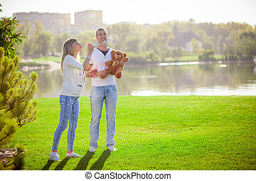 Pregnant couple on a riverbank in summer