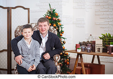 Father and young son near decorated Christmas tree at home
