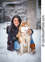 Young woman with wolf dog in snow husky dog