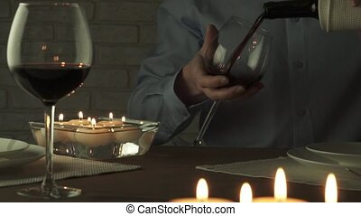 Man pours glass of red wine at candlelight romantic evening...