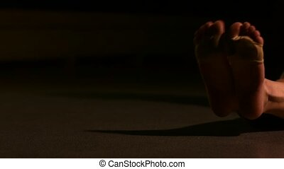 Female teen dancer sitting on the floor in ballet class and stretching legs.
