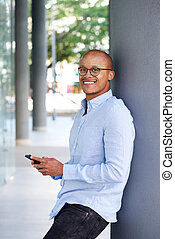 Casual businessman smiling with cellphone - Portrait of...