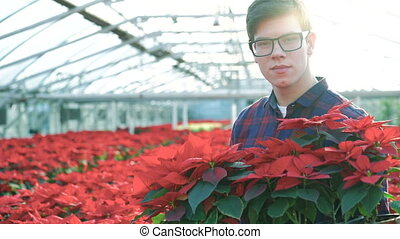 Happy gardener shows red flowers and smiling to camera