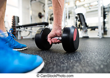 Unrecognizable senior man in gym working out with weights -...