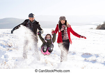 Father and mother with their daughter, playing in the snow.