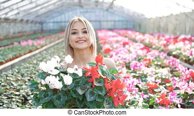 Happy pretty blonde holding flowers and smiling 4K.