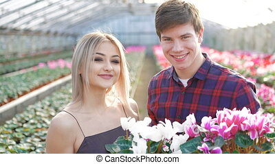 Male and female gardeners smiling to camera on flowers...