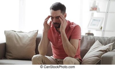 man suffering from headache at home - health care, pain,...