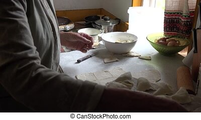 Senior woman hands prepare dumplings with curd in rural kitchen room.