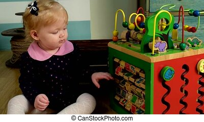 Cute little girl sitting on the floor and playing - Little...