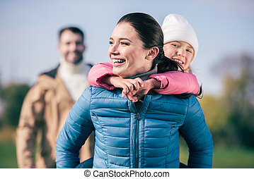 Cheerful mother piggybacking little daughter - Cheerful...