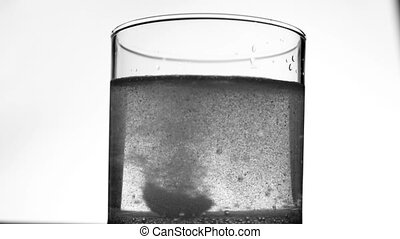 Effervescent Antacid Tablet in Glass of Water on White