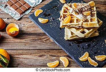 Wooden table with homemade waffles, tangerines, chocolate