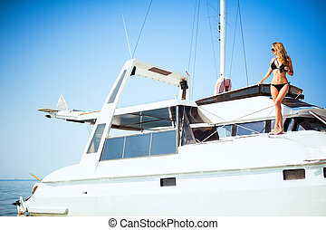 Woman with binoculars standing on a big white yacht in the...