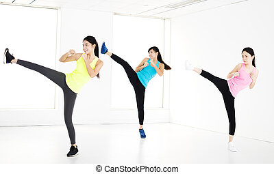 smiling young fit group stretching and kick