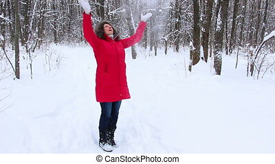 Attractive senior woman in the winter snow wood in red coat having fun