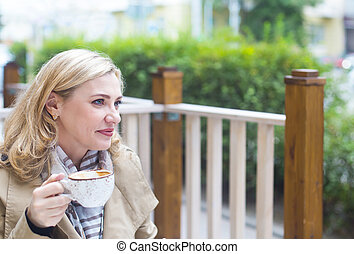 Close up happy adult blond woman with cup of coffee looking...