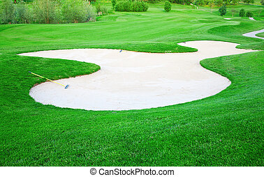 Sand trap on the green grass of the golf field
