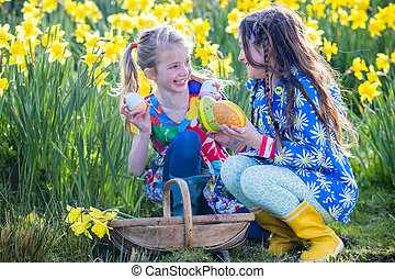 Easter Egg Hunt Teamwork - Two little girls are in a...