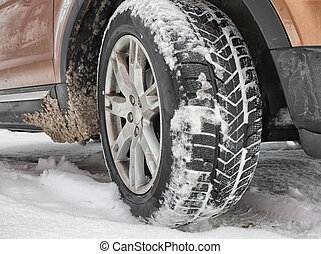 Winter tires on snow - Detail of car. Winter tire standing...