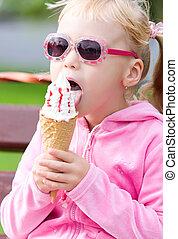 Little blond girl eating ice-cream