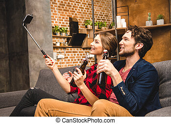 couple taking selfie - Happy couple with beer, taking selfie