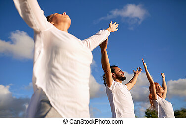 group of people making yoga or meditating outdoors -...