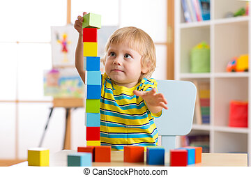 child boy playing with block toys in day care center