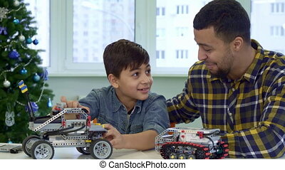 Father and son play with toy SUV - Brunette father and son...