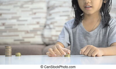 Asian little girl stacking coins