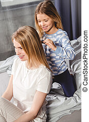 Daughter combing hair of mother - Smiling little daughter...