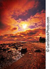 sunset on a beach - crimson sunset on a beach
