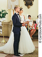 Bride and groom hold candles standing in the crowns in a church