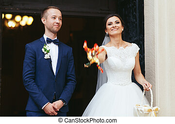 Bride throws sweets standing with a groom in the church entrance