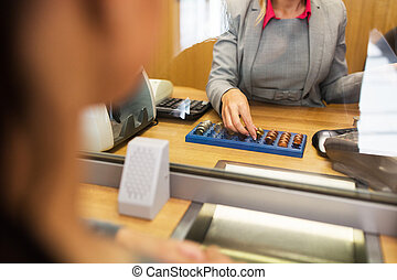 clerk counting cash money at bank office - people, money,...