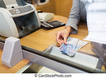 clerk with swiss francs cash money at bank office - people,...