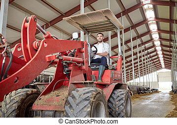man or farmer driving tractor at farm - farming, agriculture...